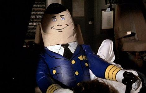"""Kadr z filmu """"czy leci z nami pilot"""" przedstawiający nadmuchiwaną lalkę w mundurze pilota siedzącą za sterami samolotu"""